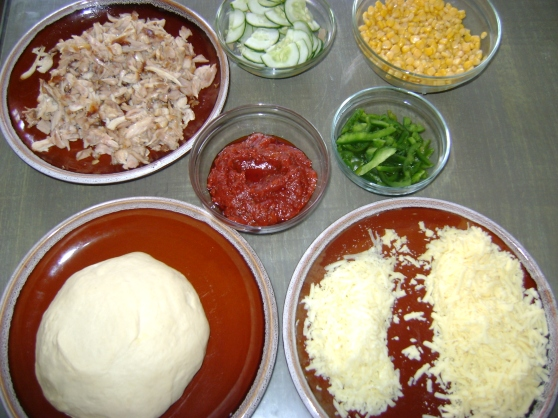 From top left to right: flaked chicken, cucumber, sweetcorn, tomato sauce, green pepper, pizza base dough, Mozzarella, cheese and Cheddar cheese.